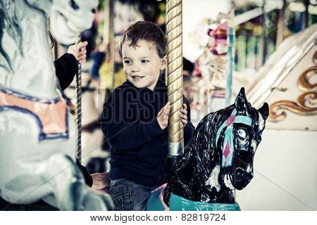Happy Boy On A Carousel Horse