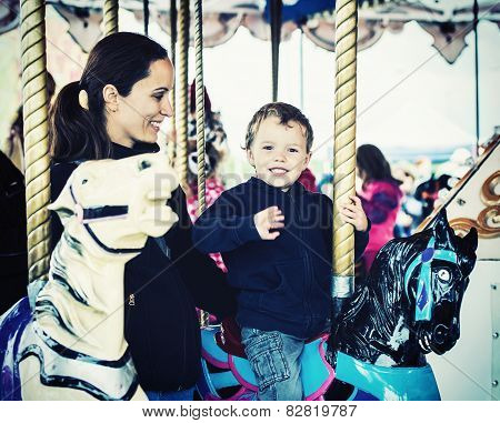 Boy Waving On A Carousel Ride With Mother - Retro