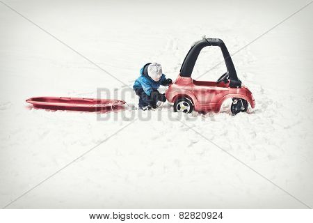 Young Boy Attaching A Red Sled To His Toy Car