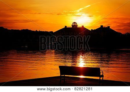 Silhouetted Park Bench By The Lake At Sunset
