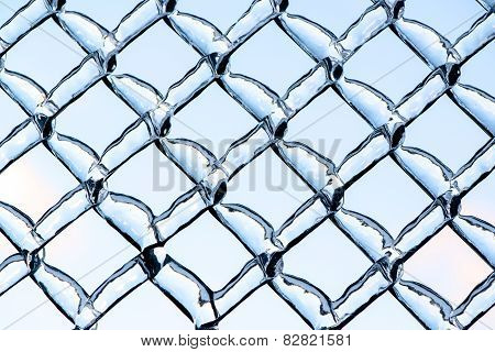 Blue Sky Refracted By Ice On A Metal Chain Link Fence