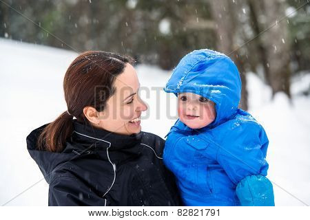 Mother Smiling At Baby Son Outside In The Winter