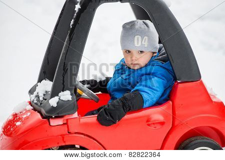 Young Boy Sitting In A Toy Car Stuck In The Snow - Close Up