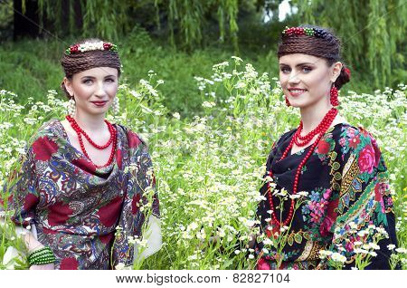 Two Caucasian Slavonic Women Sitting In Thr Field Of Flowers