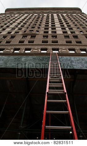 Red ladder leaning building