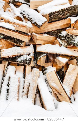 Stacked chopped firewood covered by snow
