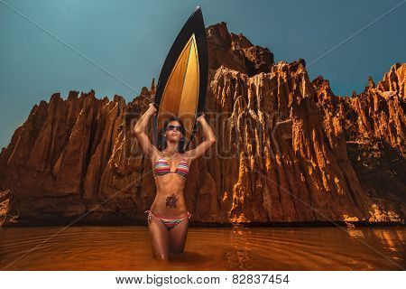 Beautiful young brunette woman with a surf board on a stunning beach against picturesque red mountains.