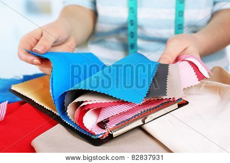 Colorful fabric samples in female hands on table and light blurred background
