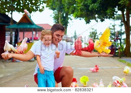 Happy Family Feeding Colorful Pigeons On Animal Farm