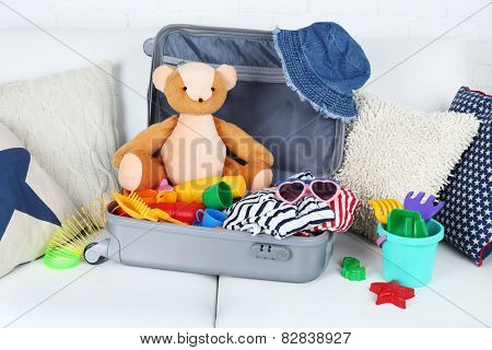 Suitcase packed with clothes and child toys on sofa with pillows and white brick wall background