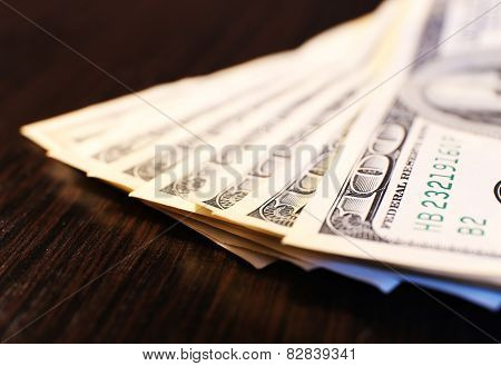 One hundred dollars banknotes on wooden table background
