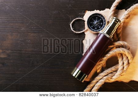 Marine still life spyglass, compass rope and sheet of paper on wooden background