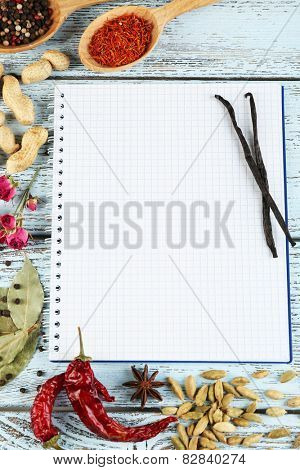 Spices with recipe book on color wooden table background