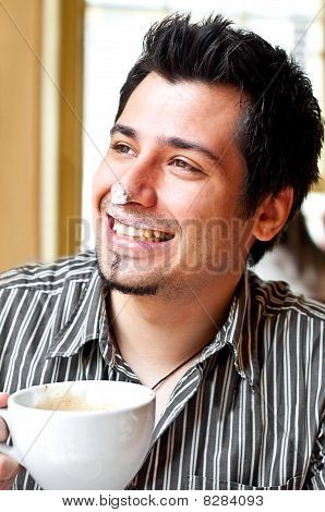 Portrait Of A Happy Young Man Drinking Cappuccino
