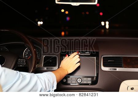 Woman driving his modern car at night in city, close-up