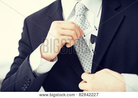 close up of mans hand hiding ace in the jacket pocket