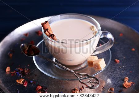 Black tea with milk in glass cup with lump sugar and spiced on metal tray and color wooden planks background