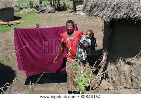 Maasai Village, Dark-skinned Woman Holds A Child.