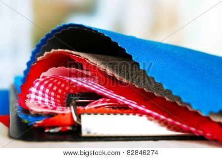 Colorful fabric samples on table and light blurred background
