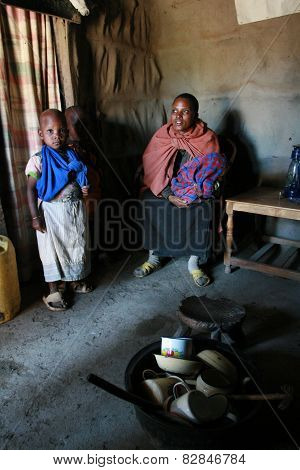 Maasai Family Inside Their Huts, A Black Woman And Children.