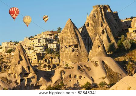 Hot air balloons flying over Cappadocia near Uchisar castle at sunrise, Turkey