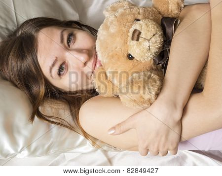 Girl lying in the bed with the soft toy