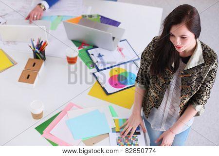 Portrait of attractive female  designer in office, sitting