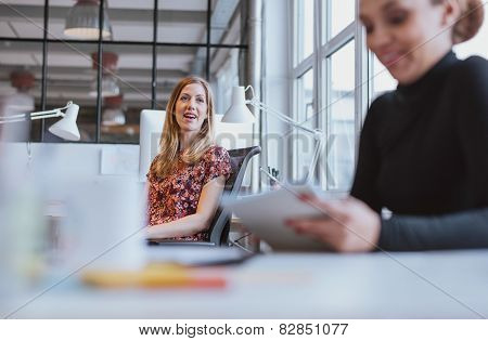 Young Woman Having Friendly Chat With Her Colleague