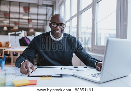 Confident Young Man At His Desk