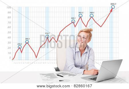 Beautiful young businesswoman calculating stock market with rising graph in the background