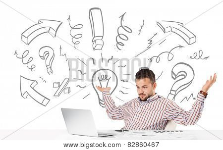 Good-looking young businessman brainstorming with drawn arrows and symbols