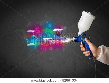 Worker with airbrush and colorful abstract clouds and balloons concept