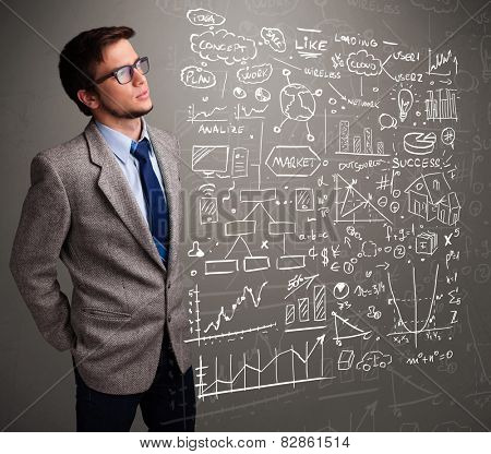 Attractive young man looking at stock market graphs and symbols