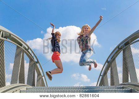 Two enthusiastic girls jumping on bridge