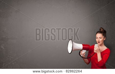 Pretty girl shouting into megaphone on copy space background