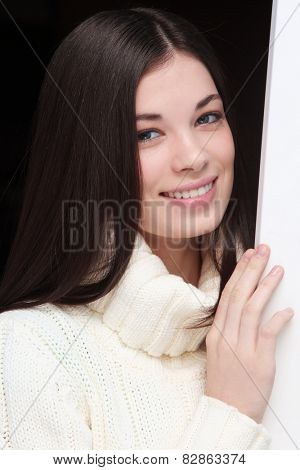 Casual portrait of young beautiful smiling girl in white pullover