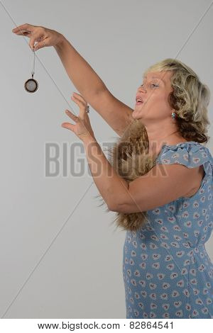 Mature blonde woman holding a tea strainer