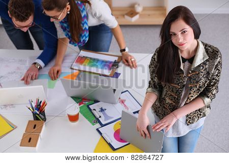 Portrait of attractive female  designer in office, sitting