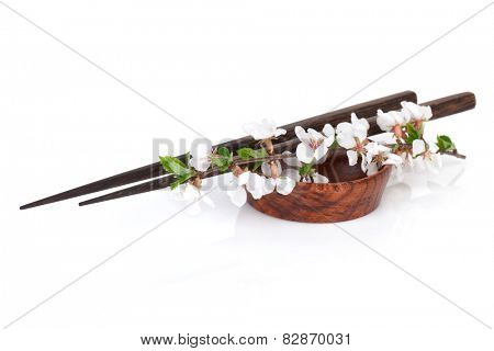 Chopsticks and sakura branch over soy sauce bowl. Isolated on white background