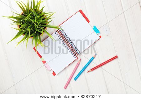 Whtie wooden table with flower, blank notepad and colorful pencils. View from above with copy space