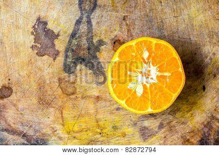 Orange cut in half on old chopping board