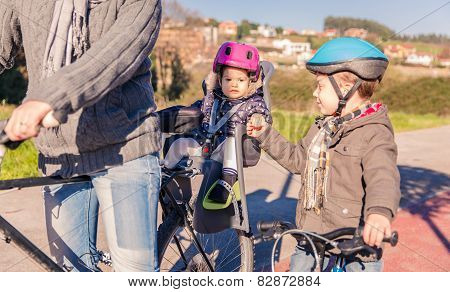 Lttle girl with helmet on head sitting in bike seat
