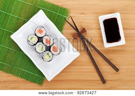 Sushi maki set and soy sauce on bamboo table