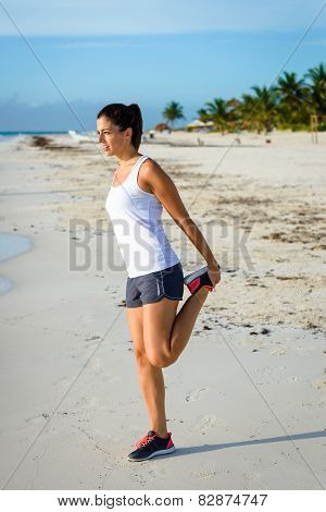 Woman Stretching Leg After Running At Beach
