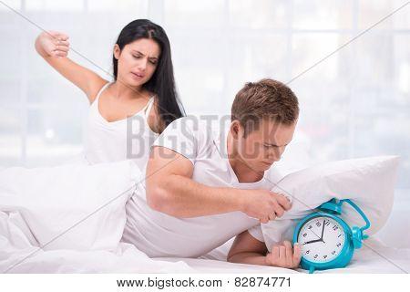 Sleepy couple waking up by an alarm clock ringing