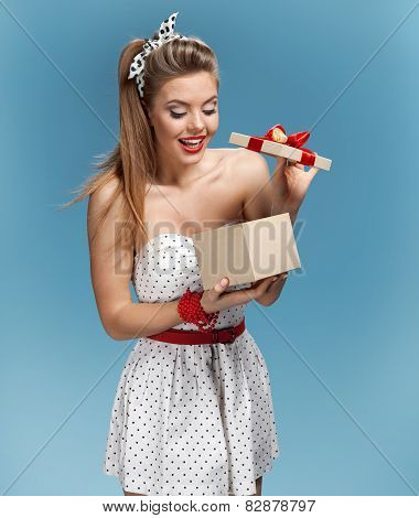 Excited young girl opening present box