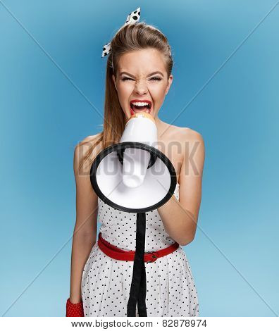 Aggressive pin-up girl screaming with megaphone, mouthpiece, speaking trumpet
