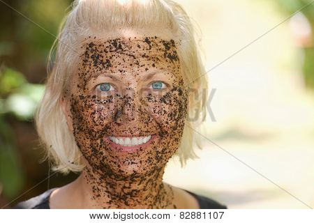 Portrait of happy woman with a coffee pilling mask