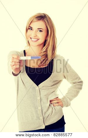 Happy smiling woman with pregnancy test