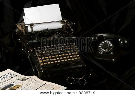 Old Type Writer With Phone , Glasses And Newspaper